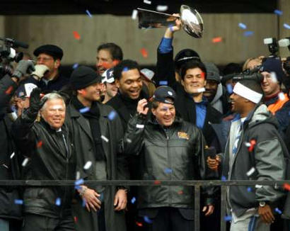 New England Patriots owner Bob Kraft (L) celebrates with quarterback Tom Brady (2nd from L), defensive end Richard Seymour, head coach Bill Belichick, linebacker Tedy Bruschi  holding the Vince Lombardi Super Bowl trophy and cornerback Ty Law (R-with microphone) and the rest of the team during a victory rally held before a crowd estimated by police to number 1.5 million people in Boston February 3, 2004. The Patriots defeated the Carolina Panthers in Super Bowl XXXVIII February 1.
