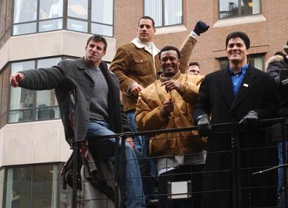 New England Patriots Mike Vrabel, Christian Fauria, Willie McGinest and Teddy Bruschi wave to fans as they ride along the Super Bowl parade route Tuesday, Feb. 3, 2004 in Boston, Mass.