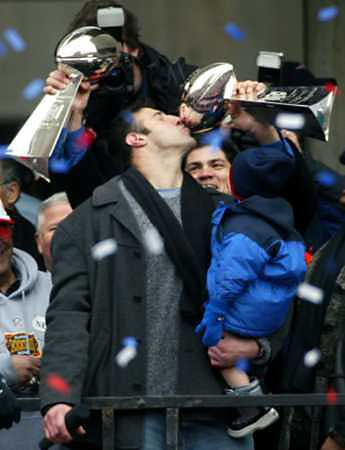 Linebacker Tedy Bruschi holds up two Vince Lombardi trophies for fellow Patriots linebacker Mike Vrabel to kiss while Vrabel's son looks on during a victory celebration before a crowd of nearly 1.5 million people in Boston February 3, 2004.